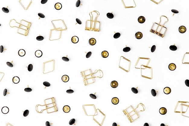 Różne spinacze do papieru i pinezki na białym tle.