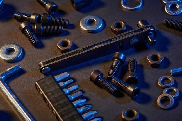 Różne śruby, nakrętki, podkładki, śrubokręty na czarnym stole. narzędzia sprzętowe i metalowe śruby, nakrętki i podkładki.