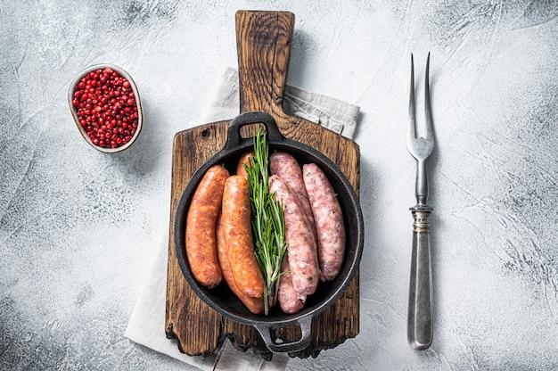 Różne surowe kiełbaski chorizo i bratwurst z przyprawami na patelni z rozmarynem. widok z góry.