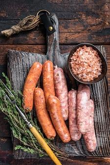 Różne surowe kiełbaski wieprzowe i wołowe z przyprawami na drewnianej desce z tymiankiem. ciemne drewniane tło. widok z góry.
