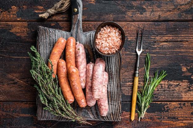 Różne surowe kiełbaski wieprzowe i wołowe z przyprawami na drewnianej desce z tymiankiem. stół z ciemnego drewna. widok z góry.