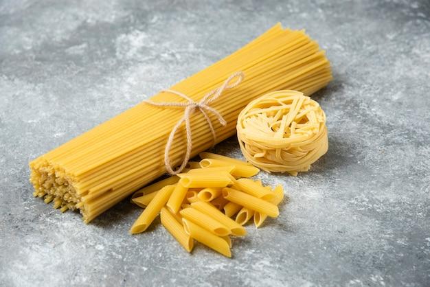 Różne surowe makarony na marmurowej powierzchni. spaghetti, penne, tagliatelle.