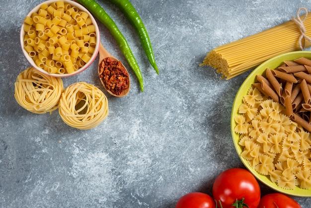Różne surowe makarony ze świeżymi warzywami na kamiennym stole