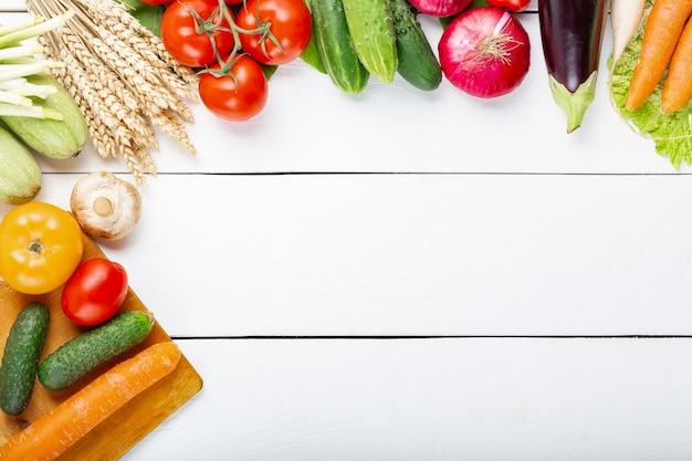 Różne surowe organiczne świeże warzywa na białym drewnianym stole. świeże jedzenie wegetariańskie w ogrodzie. jesienny obraz sezonowy rolnik stół z pieczarkami, żyto, ogórki, pomidory, bakłażan, dynia i inne.