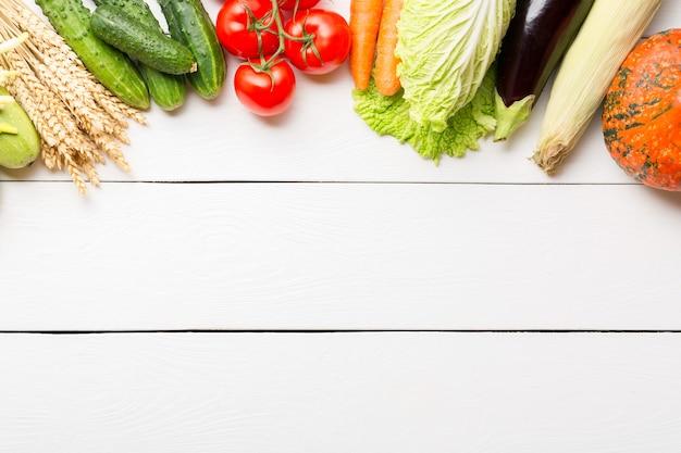 Różne surowe organiczne świeże warzywa na białym drewnianym stole.