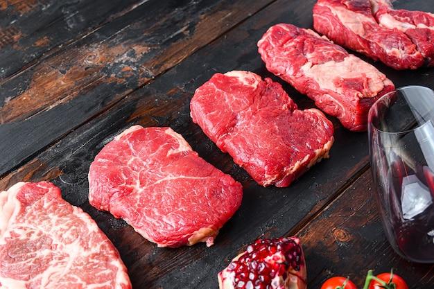 Różne surowe steki wołowe z przyprawami i czerwonym winem w butelce i szklance na starych drewnianych ciemnych deskach