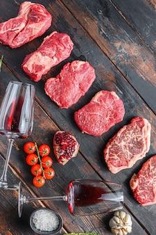 Różne surowe steki wołowe z przyprawami i czerwonym winem w butelce i szkle na starych drewnianych ciemnych deskach widok z góry z miejscem na tekst.