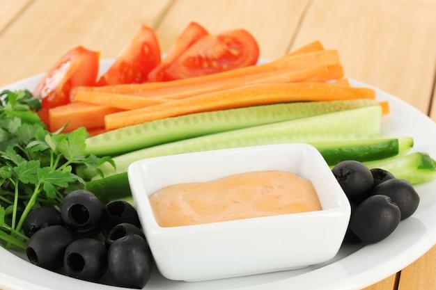 Różne surowe warzywa kije w talerzu na drewnianym stole z bliska