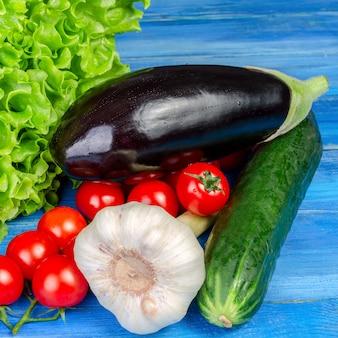 Różne surowe warzywa leżą w kupie na niebieskim drewnianym stole.