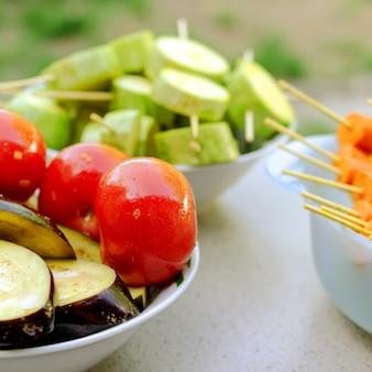 Różne surowe warzywa, nawleczone na szpikulec do grillowania. przygotowany na piknik.