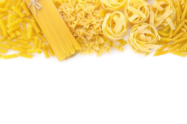 Różne surowy makaron włoski na białym tle