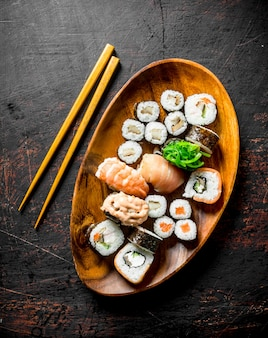Różne sushi i bułki na talerzu z patyczkami. na ciemnej rustykalnej powierzchni
