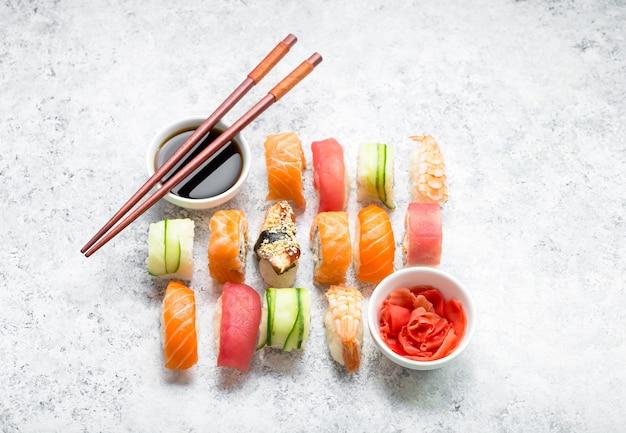 Różne sushi na białym tle betonu. japońskie sushi, bułki, sos sojowy, imbir, pałeczki.