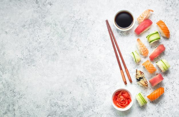 Różne sushi na białym tle betonu.