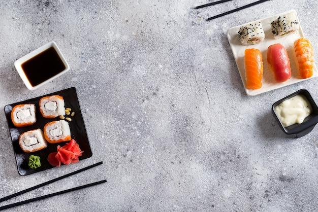 Różne sushi na czarno-biały talerz z kijami, sos na jasnym tle kamienia