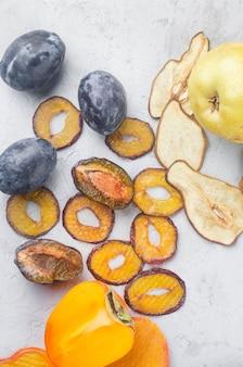 Różne suszone frytki i dojrzałe owoce na szarym tle. chipsy owocowe. koncepcja zdrowego odżywiania, przekąska, bez cukru. widok z góry, kopia przestrzeń.