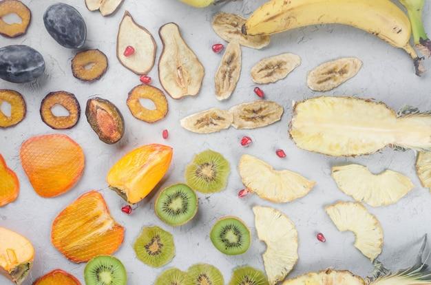 Różne suszone frytki i dojrzałe owoce na szarym tle. chipsy owocowe. koncepcja zdrowego odżywiania,