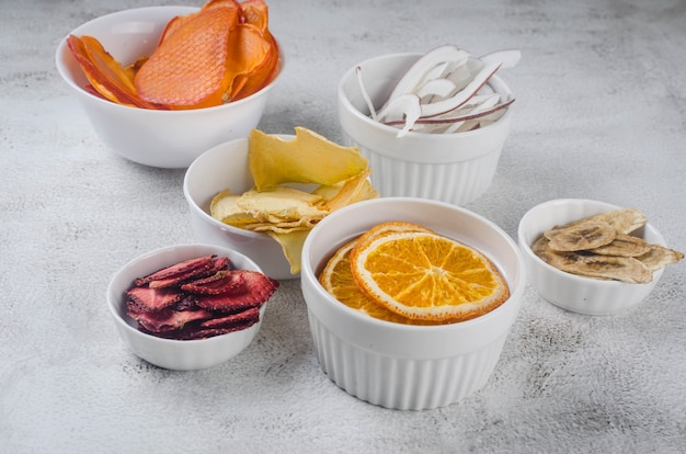 Różne suszone frytki i dojrzałe owoce w płytach na szarym tle. chipsy owocowe. zdrowe odżywianie