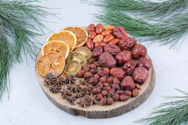 Różne suszone owoce i goździki na kawałku drewna.