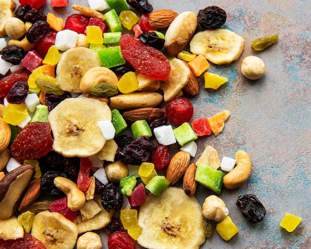 Różne suszone owoce i orzechy mieszane na szarym betonowym stole.