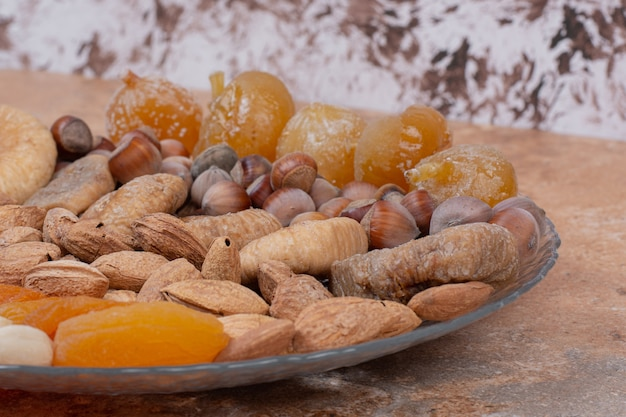 Różne suszone owoce i orzechy na szklanym talerzu.