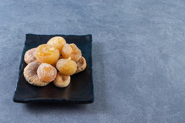 Różne suszone owoce w misce na podstawce na marmurowej powierzchni