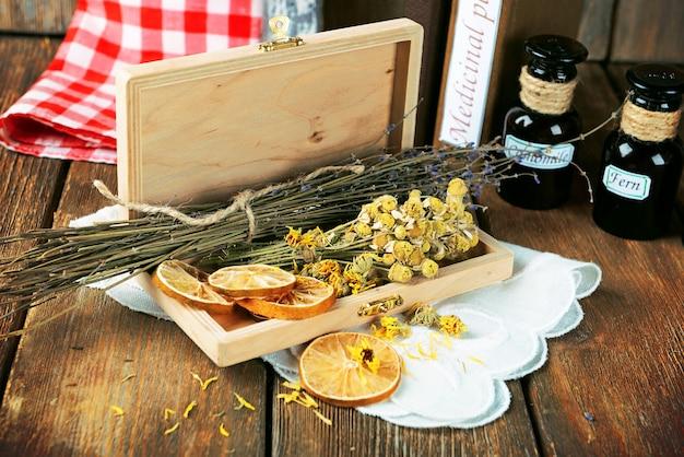 Różne suszone zioła i cytryna na stole z bliska