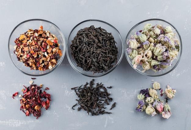 Różne suszone zioła w szklanych misach na płaskiej powierzchni gipsu.