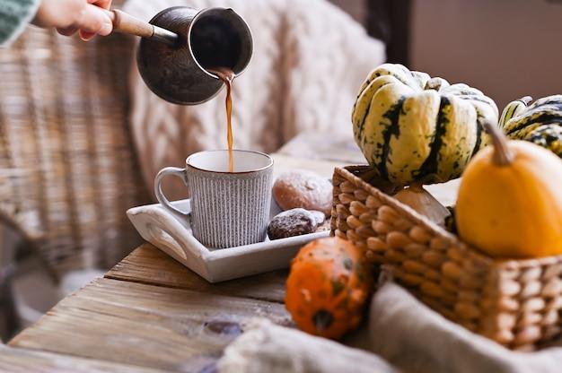 Różne święto dziękczynienia mini dynie na rustykalnym drewnianym stole i filiżankę kawy na stole.
