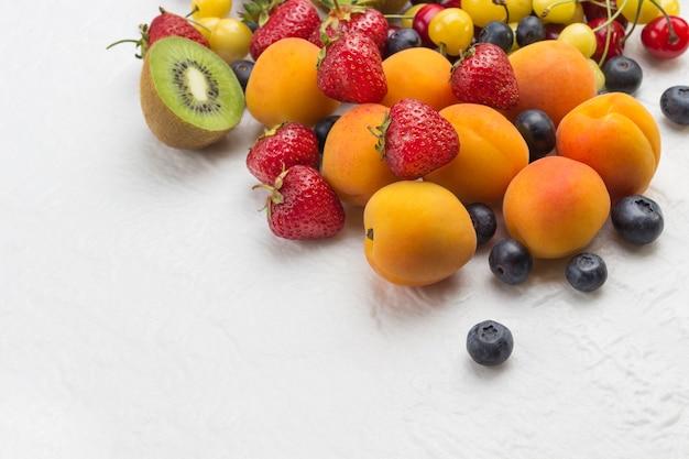 Różne świeże jagody i owoce. morele kiwi truskawka czereśnia jagoda na białej powierzchni. koncepcja utraty wagi widok z góry. skopiuj miejsce.