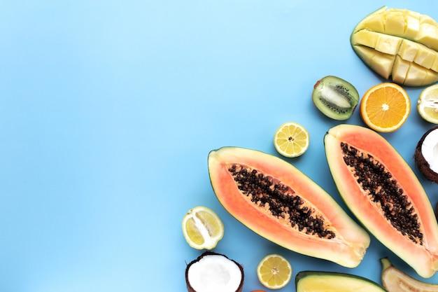 Różne świeże owoce tropikalne cięte na niebieskim tle. papaja, pomarańcza, banan, kokos, mango, kiwi i cytryna, widok z góry.