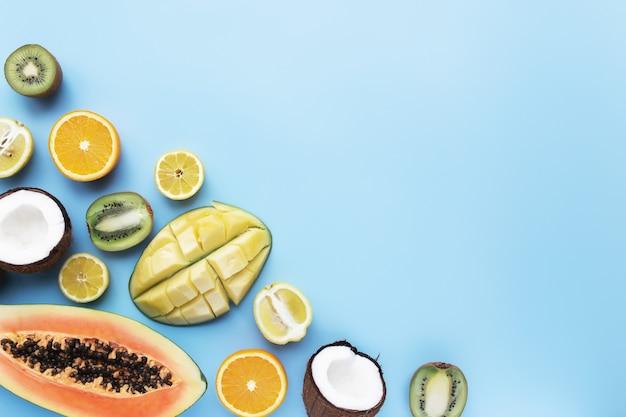 Różne świeże owoce tropikalne cięte na niebieskim tle. papaja, pomarańcza, banan, kokos, mango, kiwi i cytryna