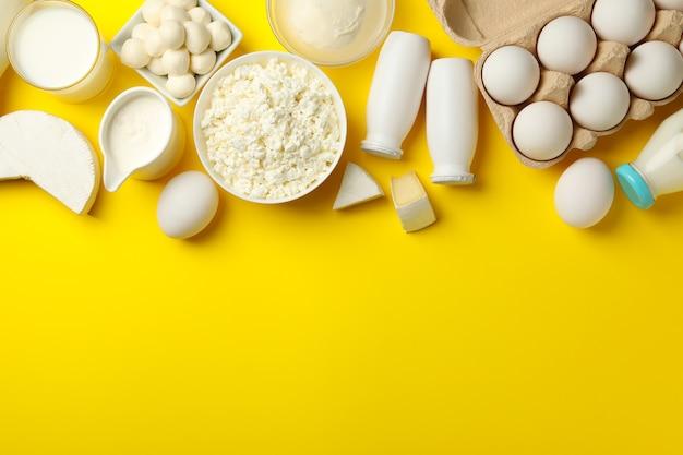 Różne świeże produkty mleczne na żółtym tle, widok z góry