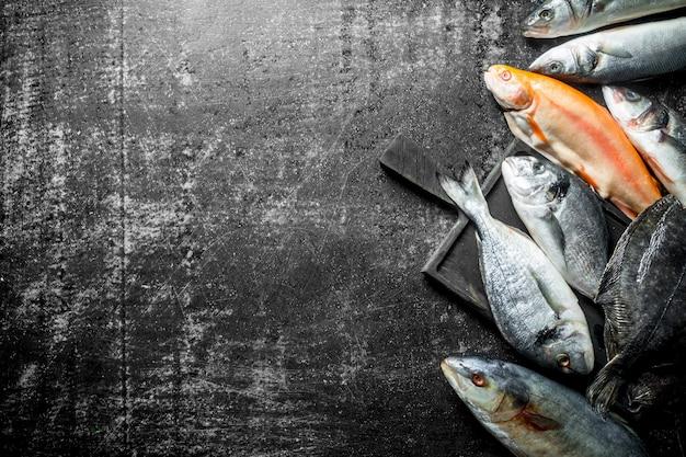 Różne świeże ryby na drewnianej desce do krojenia. na ciemnym rustykalnym stole