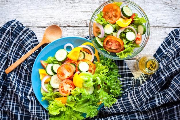 Różne świeże sałatki mix z pomidorami, ogórkiem, cebulą, papryką, zdrową żywnością i dietą m