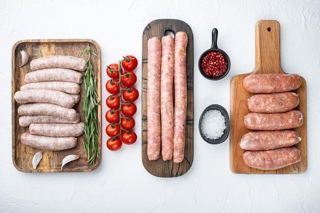 Różne świeże surowe kiełbaski wieprzowe, wołowe i drobiowe, widok z góry, na białym stole