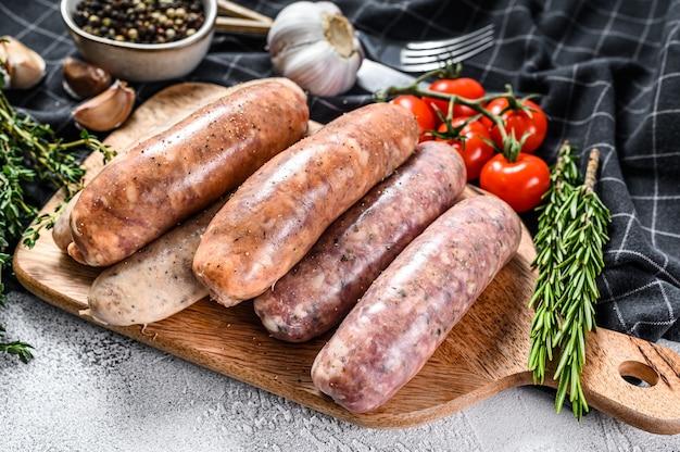 Różne świeże surowe kiełbaski wieprzowe, wołowe i drobiowe z przyprawami. szare tło. widok z góry.