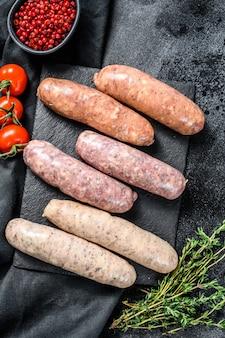 Różne świeże surowe kiełbaski wieprzowe, wołowe i drobiowe z przyprawami