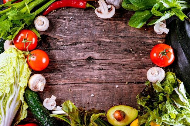 Różne świeże warzywa na drewnianym tle z teksturą, wolne miejsce na tekst.