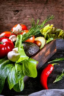 Różne świeże warzywa w drewnianym pudełku, zdjęcie pionowe.
