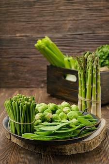 Różne świeże zielone warzywa na powierzchni drewnianych