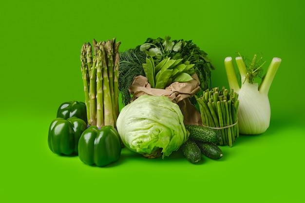 Różne świeże zielone warzywa na zielonej powierzchni