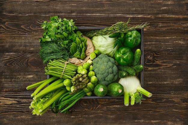 Różne świeże zielone warzywa w drewnianym pudełku na powierzchni drewna