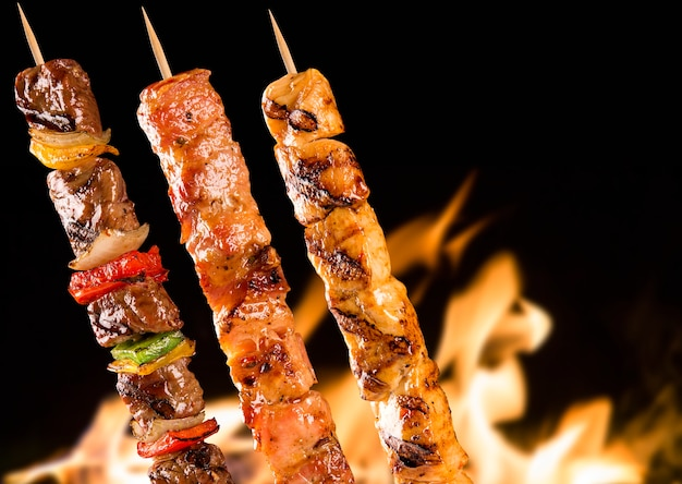 Różne szaszłyki stekowe nad płomieniami ognia.