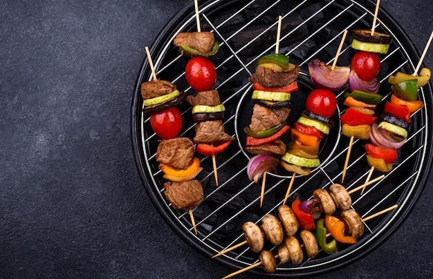 Różne szaszłyki z grilla z mięsem, pieczarkami, kiełbasą i warzywami na szaszłykach