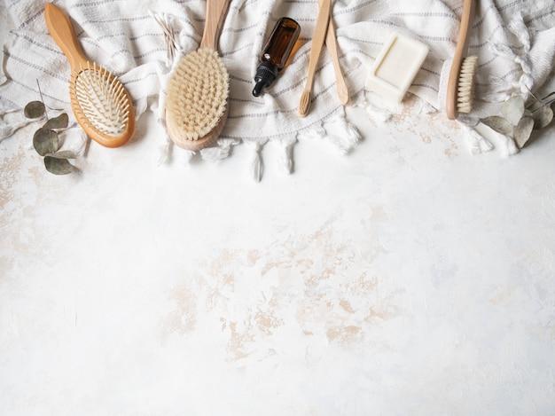 Różne szczotki do ciała, biały bawełniany ręcznik, pumeks, bambusowa szczoteczka do zębów, aromatyczny olej i mydło. koncepcja zero odpadów. ekologiczny zestaw do kąpieli. widok z góry