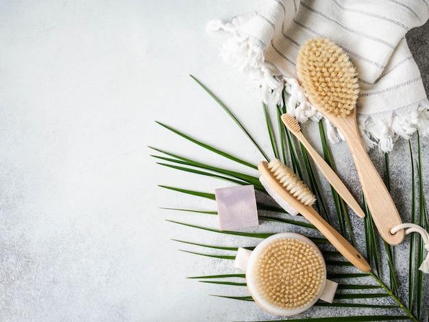 Różne szczotki do ciała, pumeks, bambusowa szczoteczka do zębów, biały ręcznik i mydło na szarym tle. koncepcja zero odpadów. ekologiczny zestaw do kąpieli. widok z góry. skopiuj miejsce