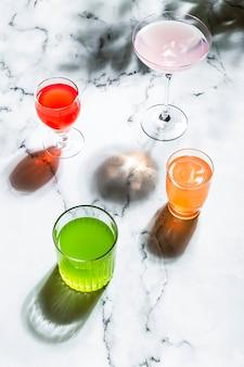 Różne szklanki z jasnymi kolorowymi napojami, w bezpośrednim ostrym świetle, długich cieniach i marmurowym tle