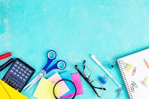 Różne szkolne dostawy na błękitnym tle. koncepcja powrót do szkoły