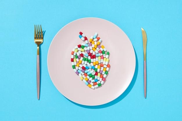 Różne tabletki i suplementy jako pokarm na okrągłym białym talerzu w postaci ryb na niebieskiej ścianie. pigułki i suplementy diety dla koncepcji diety. leżał na płasko